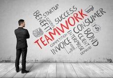 Geschäftsmann im vollen Wachstum, das weiße Wand mit Skizzen der Teamwork-Bildung betrachtet Lizenzfreie Stockfotos