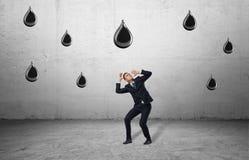 Geschäftsmann im vollen Wachstum schützt sich gegen enorme fallende Öltropfen Lizenzfreie Stockbilder