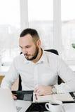 Geschäftsmann im weißen Hemd am Schreibtisch, Stockfotos