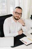 Geschäftsmann im weißen Hemd am Schreibtisch, Stockfoto