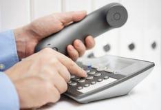 Geschäftsmann ist wählendes Telefon für Rat Stockfotos