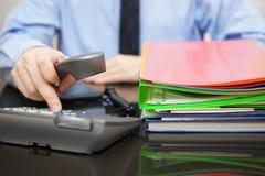 Geschäftsmann ist wählendes Telefon für Rat, als er viel FI erhielt Lizenzfreies Stockfoto