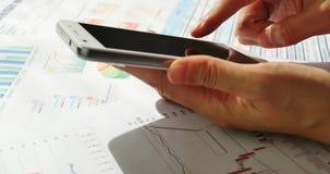 Geschäftsmann 4k, der Börsennachrichten auf SmartPhone, Finanzkreisdiagramme auf Tabelle grast stock video
