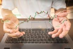 Geschäftsmann-Kontrollaktienkurve auf Arbeitsschreibtisch lizenzfreies stockbild
