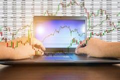 Geschäftsmann-Kontrollaktienkurve auf Arbeitsschreibtisch lizenzfreie stockfotos
