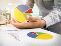 Geschäftsmann-Kontrollaktienkurve auf Arbeitsschreibtisch lizenzfreie stockfotografie