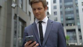Geschäftsmann lernt gute Nachrichten vom Smartphone, Investition, erfolgreicher Start stock video