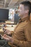 Geschäftsmann Listening Music im Büro und im Lächeln lizenzfreie stockbilder