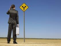 Geschäftsmann-Looking At Road-Zeichen auf Wüste Stockbild