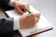Geschäftsmann macht Anmerkungen zu seinem Tagebuch Stockfotos