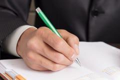 Geschäftsmann macht Anmerkungen zu seinem Tagebuch Lizenzfreie Stockfotos