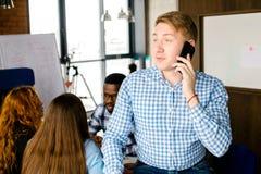 Geschäftsmann macht einen Telefonanruf im modernen Büro des Dachbodens Lizenzfreie Stockfotografie