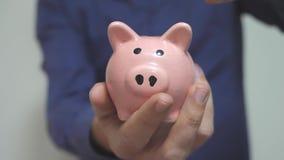 Geschäftsmann macht Spareinlagen einsetzt Lebensstilmünzen in ein Sparschwein Sparschweingeschäftskonzept Zeitlupevideo einsparun stock video footage