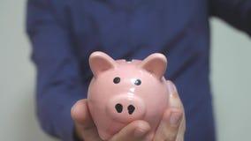 Geschäftsmann macht Spareinlagen einsetzt Münzen in ein Lebensstilsparschwein Sparschweingeschäftskonzept Zeitlupevideo einsparun stock footage
