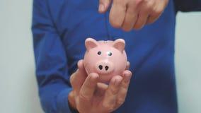 Geschäftsmann macht Spareinlagen einsetzt Münzen in ein Sparschwein Lebensstilsparschwein-Geschäftskonzept Zeitlupevideo einsparu stock footage
