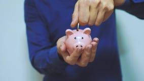 Geschäftsmann macht Spareinlagen einsetzt Münzen in ein Sparschwein Sparschweingeschäftskonzept Zeitlupevideo Rettungslebensstil stock video