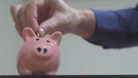Geschäftsmann macht Spareinlagen einsetzt Münzen in ein Sparschwein Sparschweingeschäftskonzept Zeitlupevideo Rettungsgeld ist stock footage