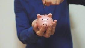 Geschäftsmann macht Spareinlagen einsetzt Münzen in ein Sparschwein Sparschweingeschäftskonzept Zeitlupevideolebensstil einsparun stock video footage