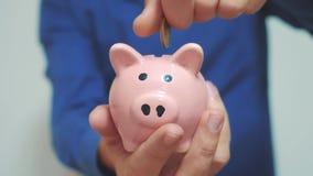 Geschäftsmann macht Spareinlagen einsetzt Münzenlebensstil in ein Sparschwein Sparschweingeschäftskonzept Zeitlupevideo einsparun stock video
