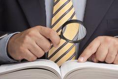 Geschäftsmann-Magnifying Glass Finding-Informations-Buch Lizenzfreie Stockfotos