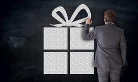 Geschäftsmann malt Geschenk auf Tafelkonzept lizenzfreie stockfotografie