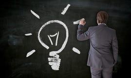 Geschäftsmann malt Glühlampe auf Tafelkonzept lizenzfreies stockbild