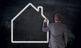 Geschäftsmann malt Haus auf Tafel Konzept stockbild