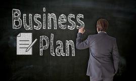 Geschäftsmann malt Unternehmensplan auf Tafelkonzept stockbild