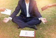 Geschäftsmann meditiert, um Druck zu entlasten Junger Geschäftsmann Stockfotos