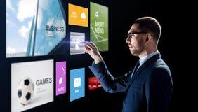 Geschäftsmann mit Anwendungen auf virtuellem Schirm stockbilder