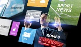 Geschäftsmann mit Anwendungen auf virtuellem Schirm stockfotografie