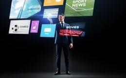 Geschäftsmann mit Anwendungen auf virtuellem Schirm lizenzfreie stockfotografie