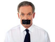 Geschäftsmann mit auf Band aufgenommenem Mund stockbild