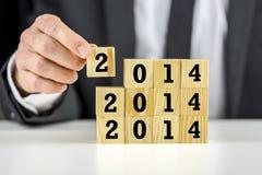 Geschäftsmann mit 2014 Bausteinen des neuen Jahres Stockfoto