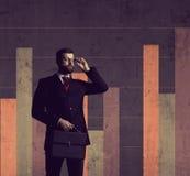 Geschäftsmann mit dem Aktenkoffer, der über Spaltendiagramm backgrou steht Stockbild