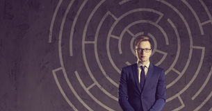 Geschäftsmann mit dem Aktenkoffer, der auf einem Labyrinthhintergrund steht B Lizenzfreie Stockfotografie
