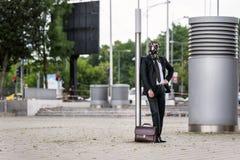 Geschäftsmann mit dem Aktenkoffer, der eine Gasmaske im Freien trägt stockbild