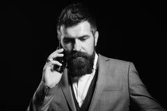 Geschäftsmann mit dem beschäftigten Gesicht lokalisiert auf schwarzem Hintergrund Mann mit langem Bart hält Handy Geschäft und Te Stockfotos