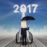 Geschäftsmann mit dem cardbord, das Nr. 2017 betrachtet Stockfotos