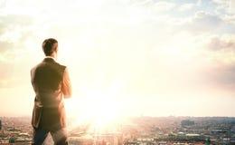 Geschäftsmann mit dem Koffer, der Sonnenuntergang betrachtet lizenzfreies stockbild