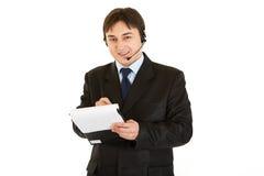 Geschäftsmann mit dem Kopfhörer, der Anmerkungen im Dokument bildet Stockfoto