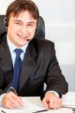 Geschäftsmann mit dem Kopfhörer, der am Büroschreibtisch sitzt Lizenzfreie Stockfotografie
