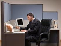 Geschäftsmann mit dem Kopfhörer, der am Schreibtisch im cubicl arbeitet Lizenzfreie Stockfotos