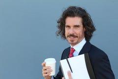 Geschäftsmann mit dem langen Haar, das Kaffeetasse hält, um zu gehen und Ordner mit Dokumenten mit Kopienraum Stockfotografie