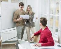 Geschäftsmann mit dem Laptop, der die Mitarbeiter sich besprechen über Dokumenten im Büro betrachtet Lizenzfreie Stockfotografie
