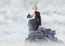 Geschäftsmann mit dem Laptop, der oben auf Felsen in den Wolken schaut Stockbild