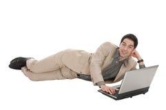 Geschäftsmann mit dem Laptoplügen Lizenzfreie Stockfotografie