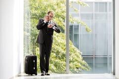 Geschäftsmann mit dem Laufkatzenkasten, der sein Uhr- und Unterhaltungso betrachtet Lizenzfreie Stockbilder