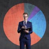 Geschäftsmann mit dem Organisator, der auf einem Diagrammhintergrund steht Geschäft, Büro, Karriere, Konzept lizenzfreie stockfotografie