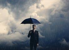 Geschäftsmann mit dem Regenschirm, der über stürmischem Hintergrund steht Busin Lizenzfreie Stockfotos
